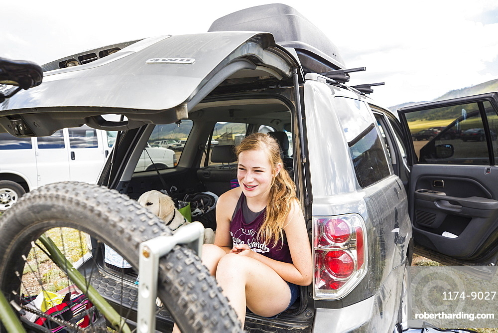 Teenage girl sitting on the tailgate of an SUV looking at vista, New Mexico, United States