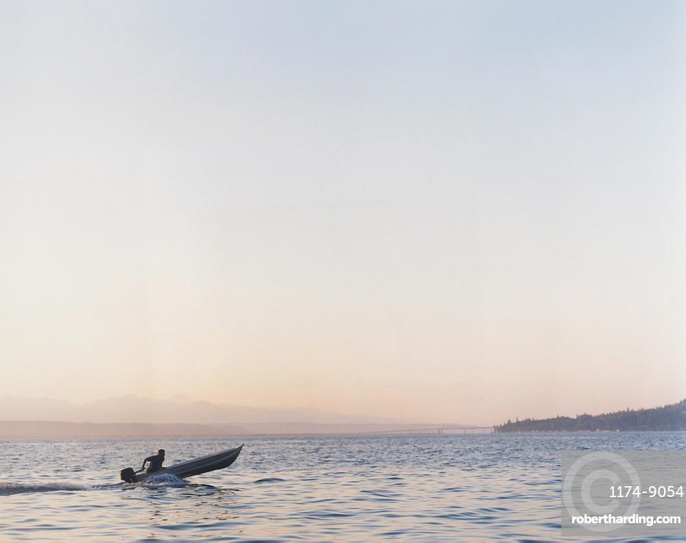 Man riding in small motorized skiff at dusk, Washington, United States
