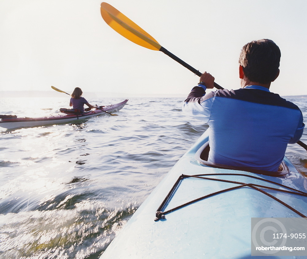 Middle aged man and woman sea kayaking on calm waters, Hood Canal, Puget Sound, Washington, United States