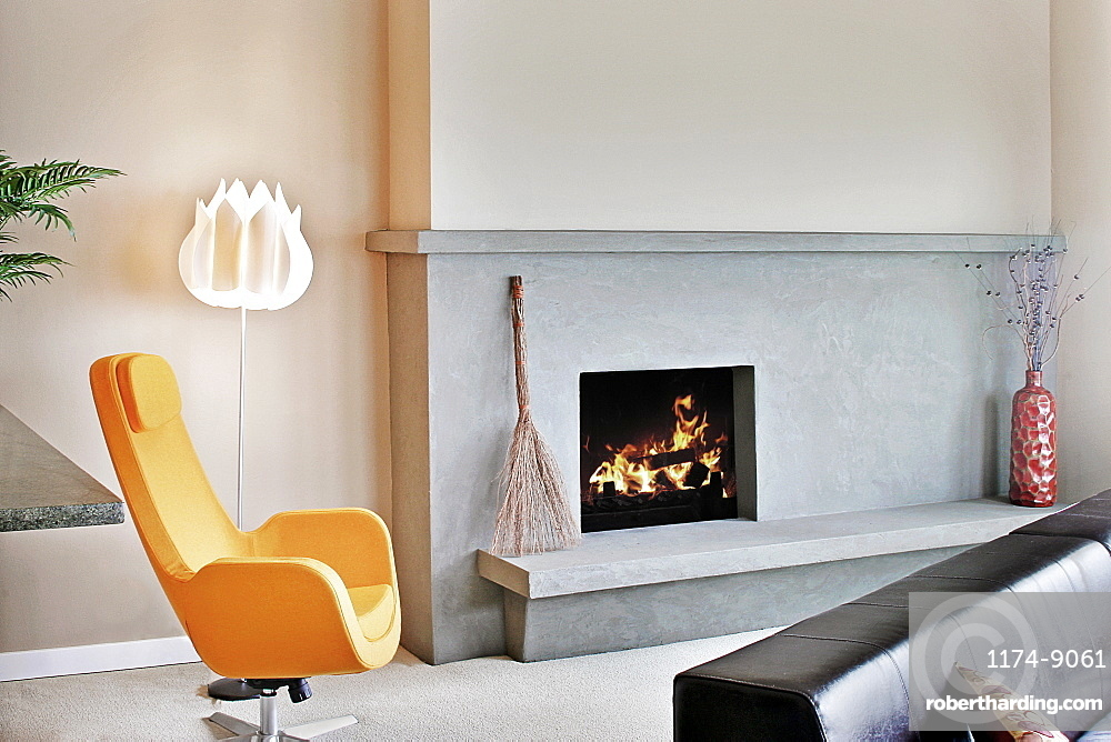 Living room in a modern house, with a fireplace and mantlepiece and hearth, and a modern yellow chair, Washington, United States