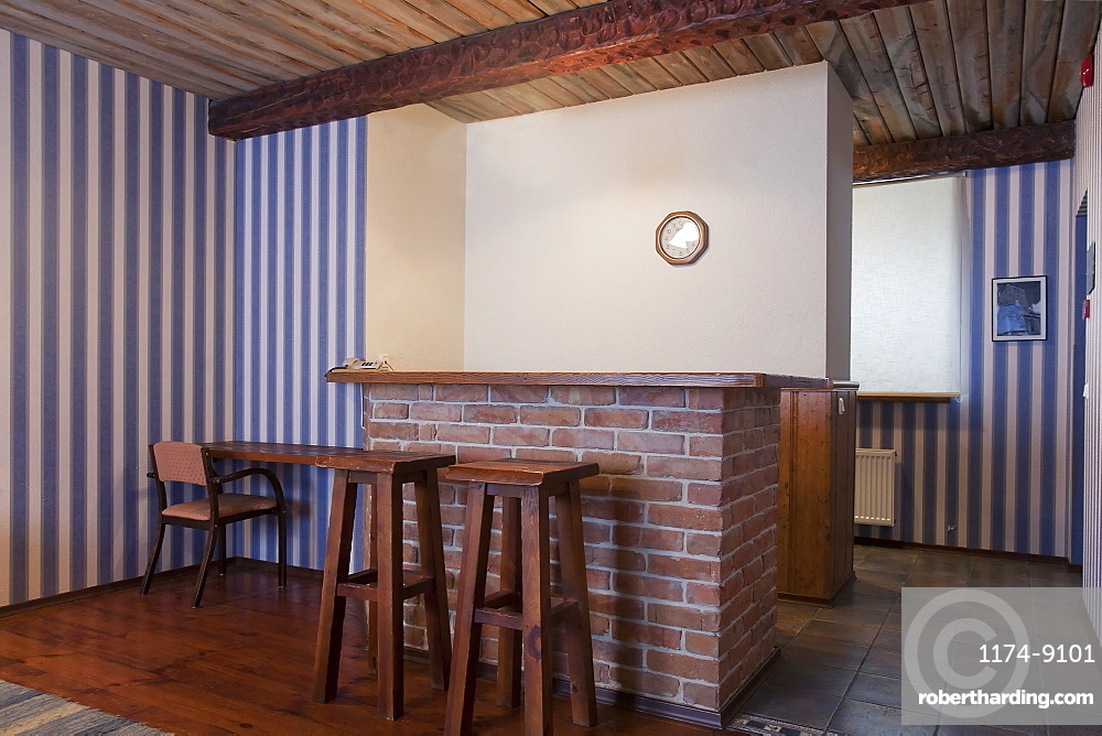 A hotel with old fashioned retro styled rooms, bar with two bar stools and striped wallpaper, Estonia