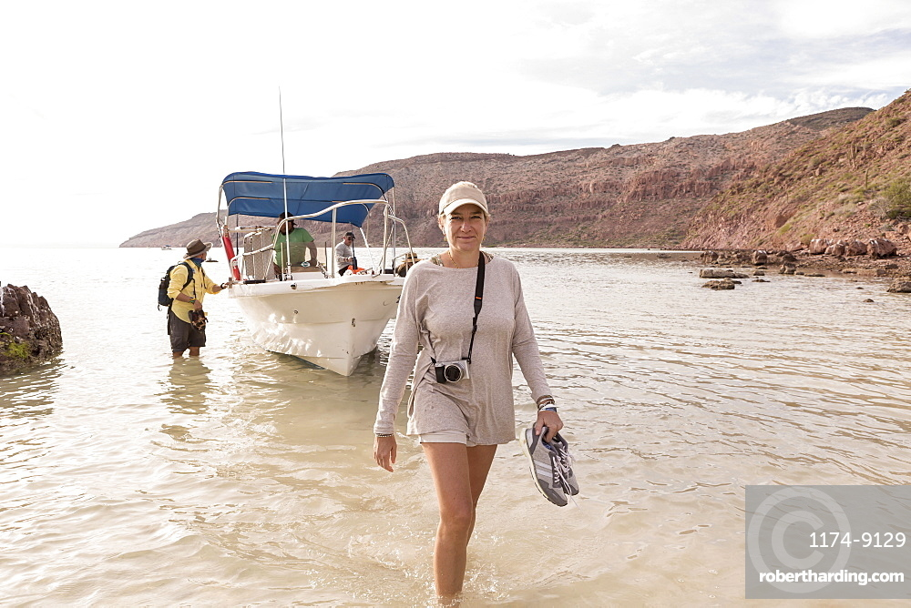 Woman walking to shore from power boat, Sea of Cortes, Mexico