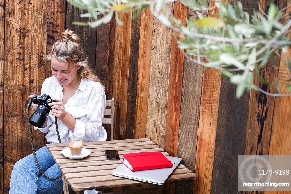 Young blond woman sitting alone at a cafe table, looking at digital camera display, Watlington, Oxfordshire, United Kingdom