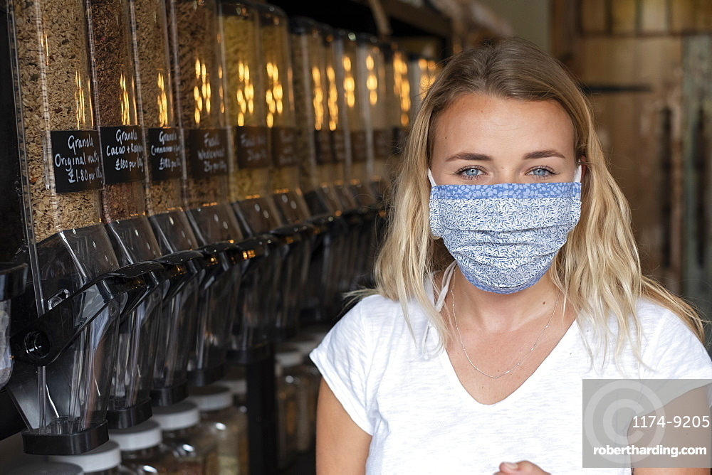 Portrait of young blond woman wearing face mask, standing in waste free wholefood store, Watlington, Oxfordshire, United Kingdom