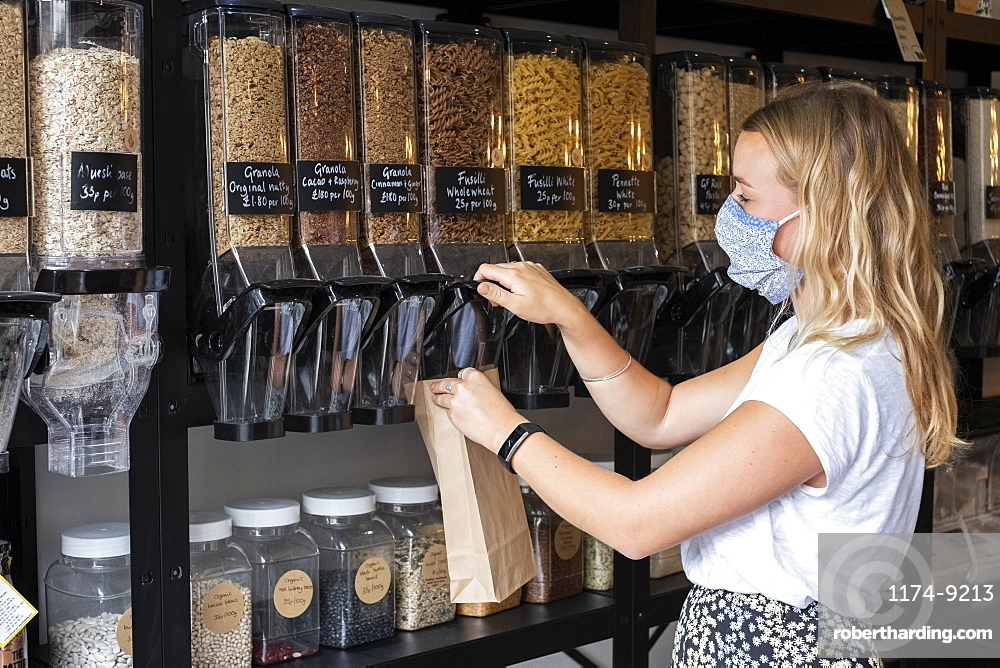 Woman wearing face mask shopping filling a paper bag with loose ingredients, Watlington, Oxfordshire, United Kingdom