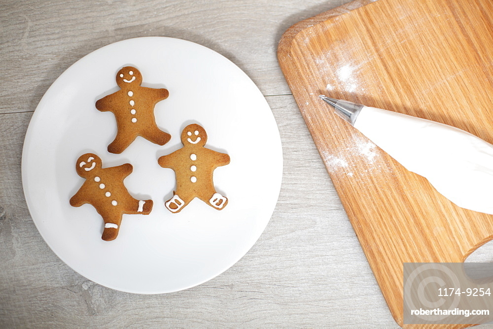 High angle close up of wooden cutting board and Gingerbread Men on a white plate