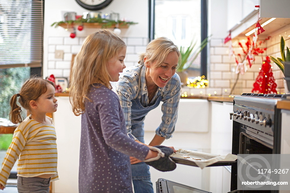 Blond woman wearing blue apron and two girls standing in kitchen, baking Christmas cookies