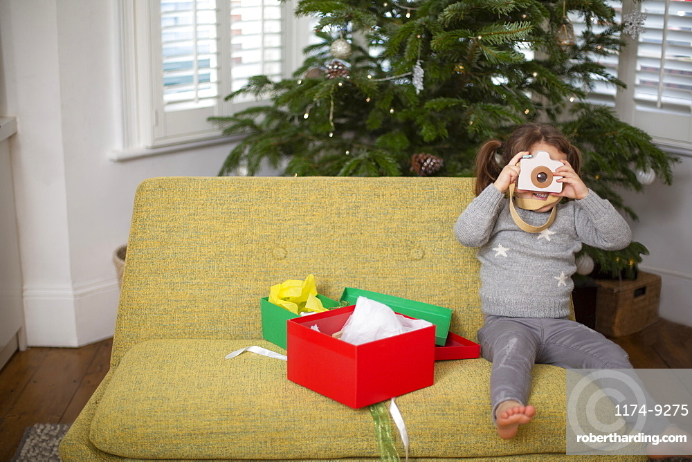 Young girl sitting on sofa with Christmas present taking picture with toy camera