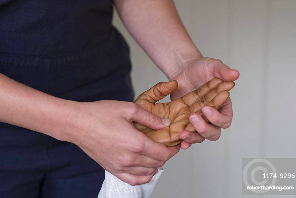 Therapist touching a client's hands