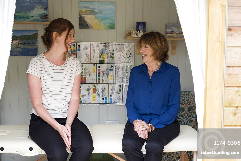 Woman and female therapist talking seated on a treatment couch