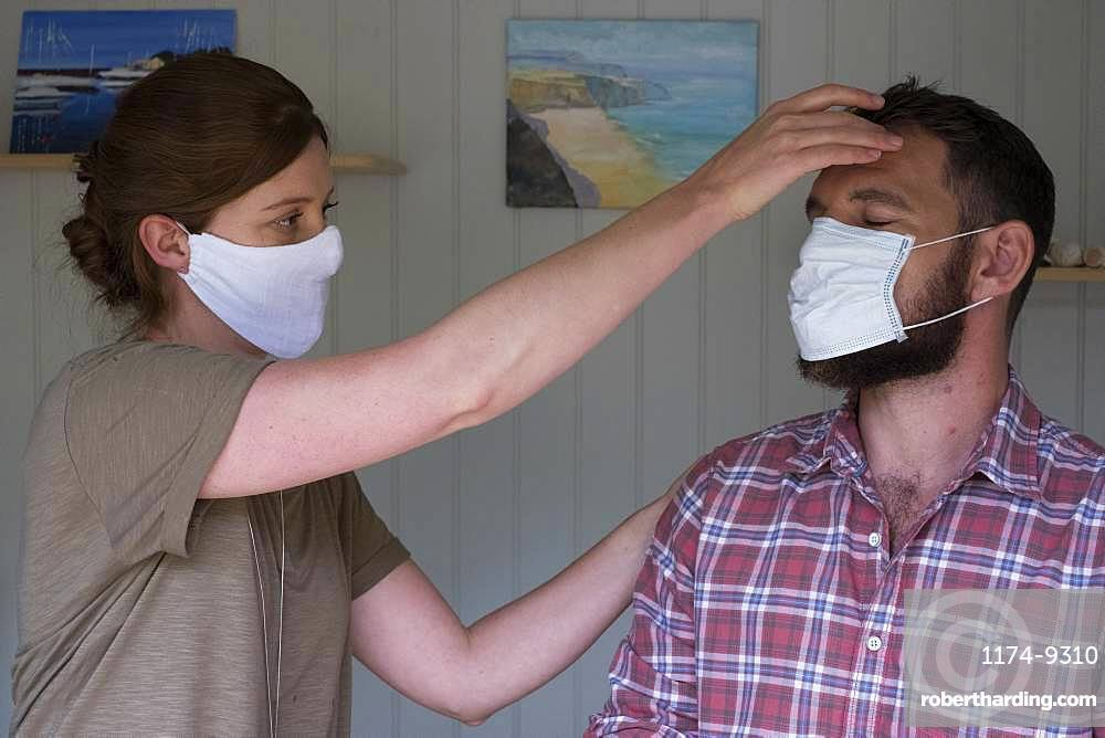 Therapist and client in face masks, in an alternative therapy session
