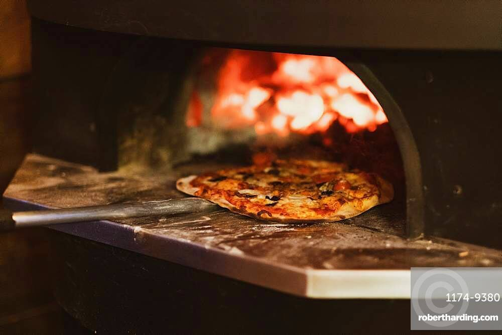 Close up of pizza in a wood-fired oven in a restaurant