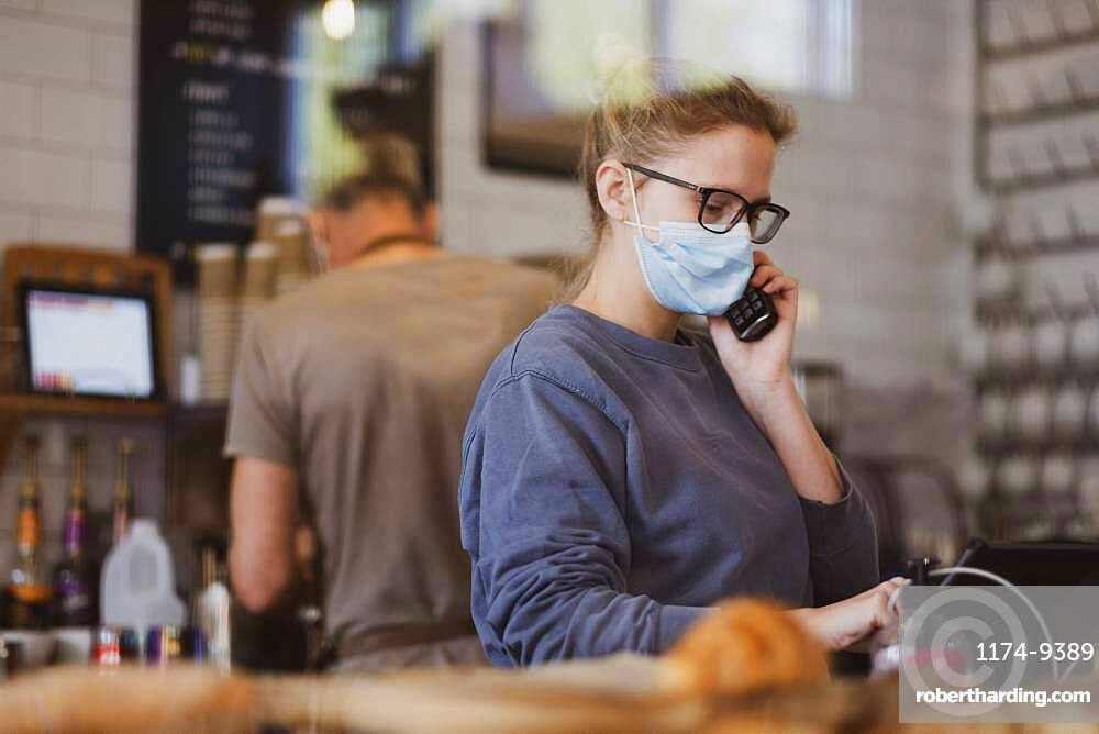 Waitress wearing face mask working in a cafe, on the phone