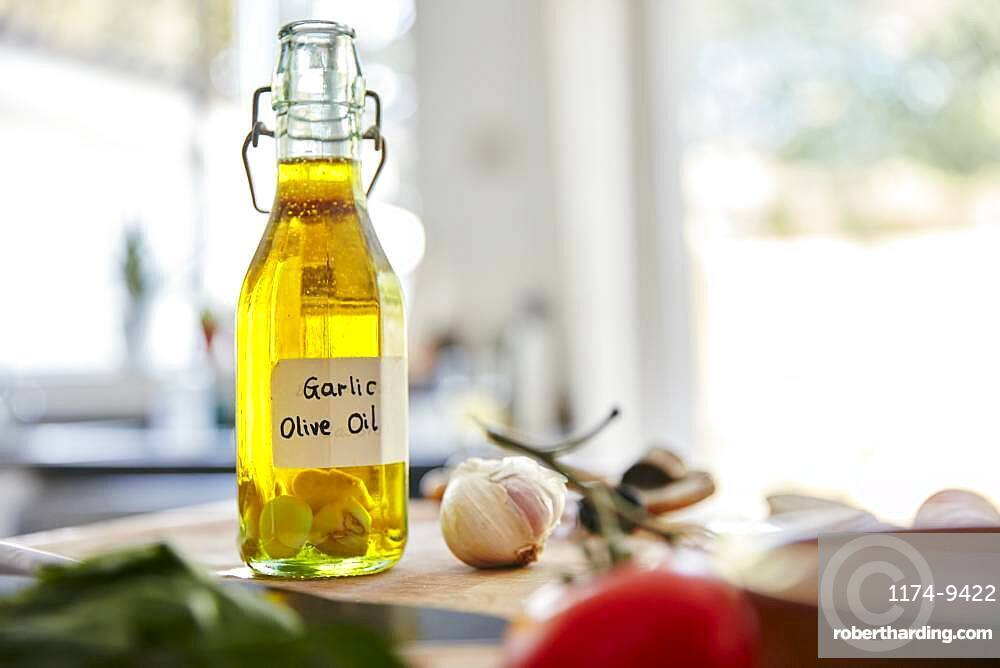 Glass bottle containing olive oil and garlic cloves standing on chopping board in kitchen