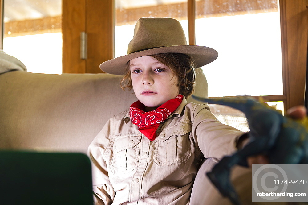 Young boy wearing safari outfit and headphones watching a movie on laptop