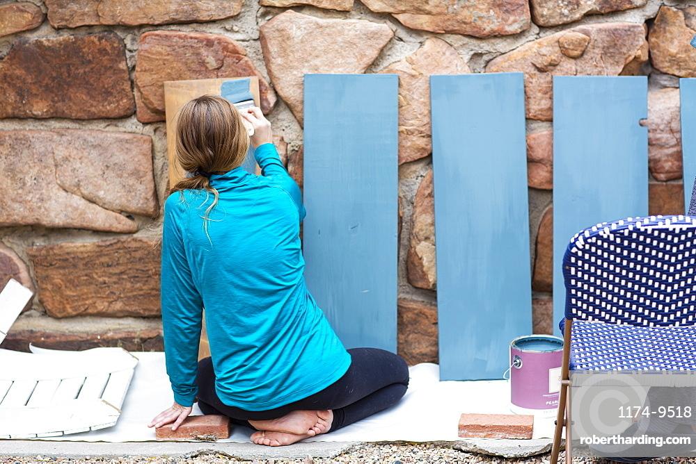 Teenage girl painting wooden shelves blue