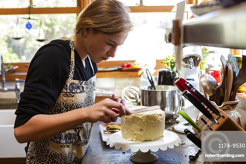 Teenage girl in kitchen applying icing to cake