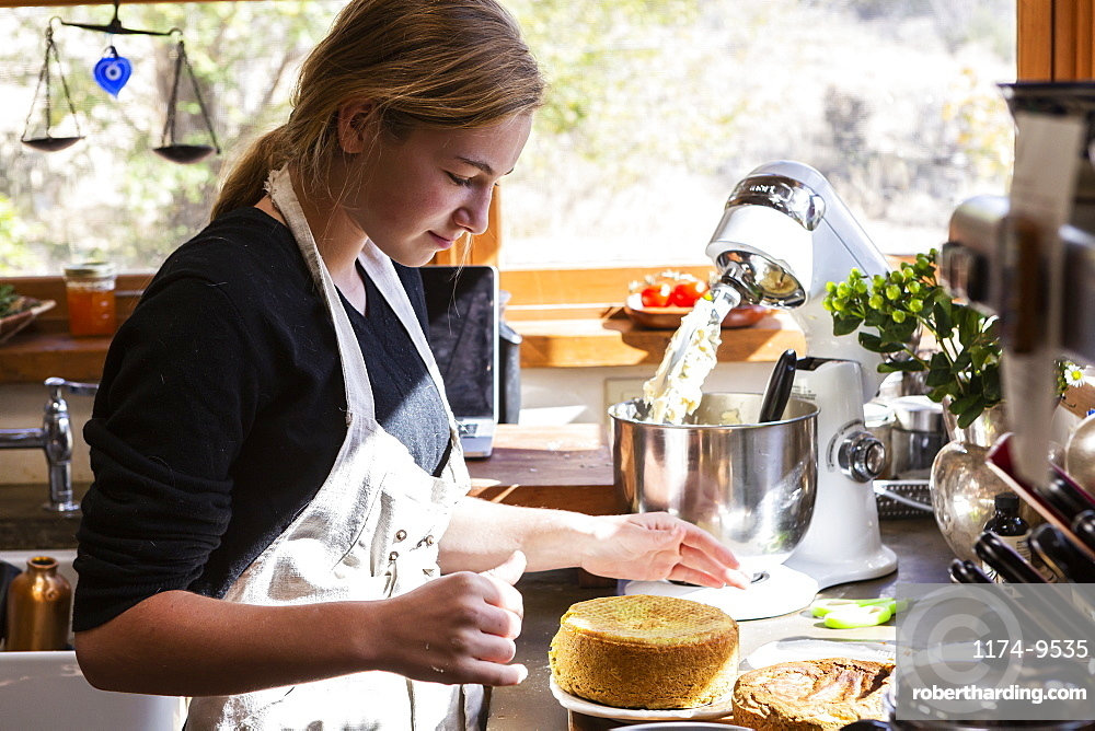 Teenage girl in kitchen baking a cake