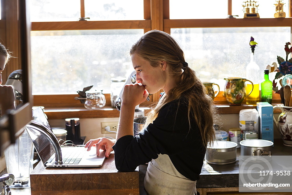 Teenage girl in a kitchen following a baking recipe on a laptop