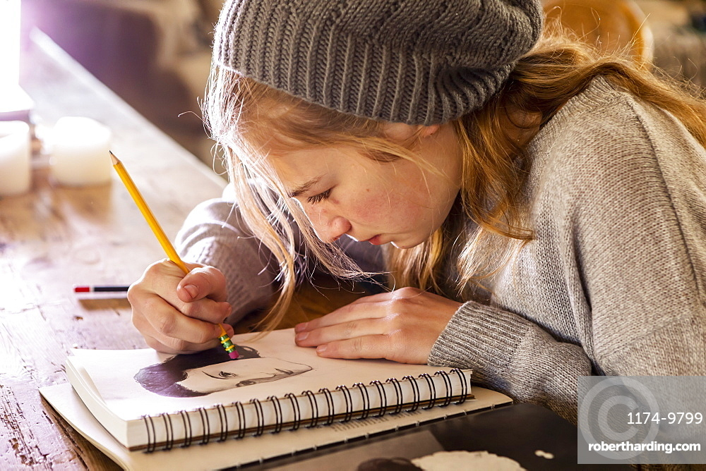 Teenage girl in a woolly hat drawing with a pencil on a sketchpad.