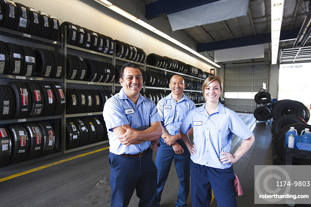 Portrait of smiling mechanics in auto repair shop, two men and a woman