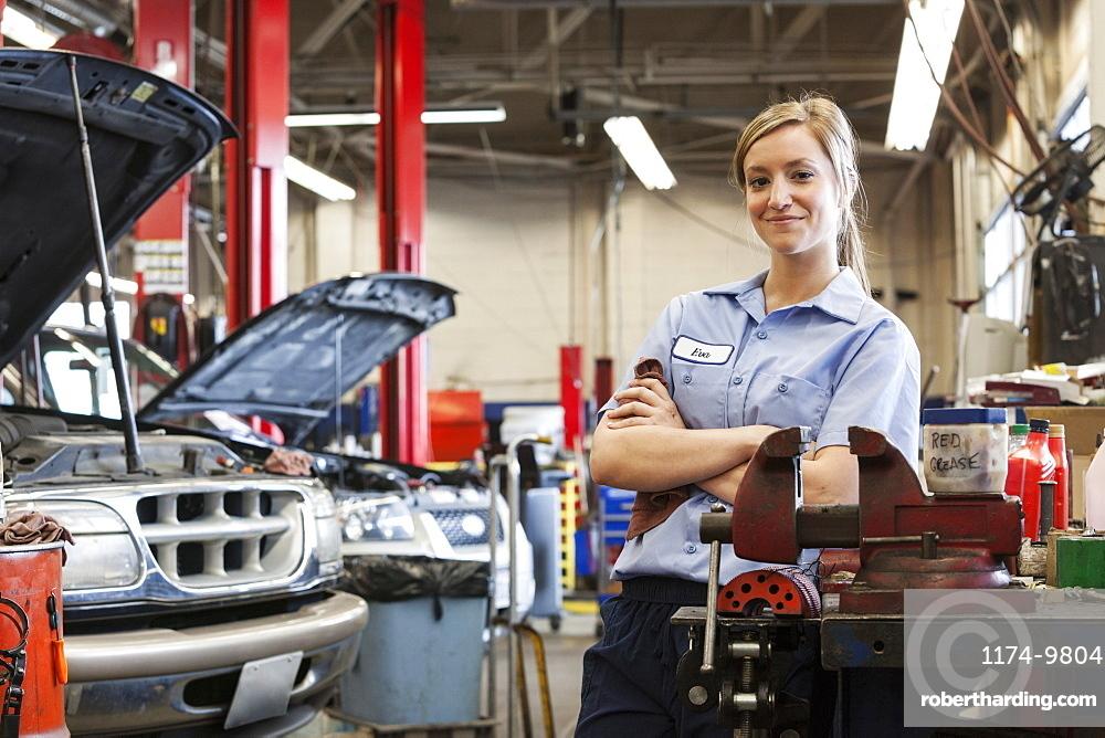 Portrait of young female Caucasian mechanic in auto repair shop