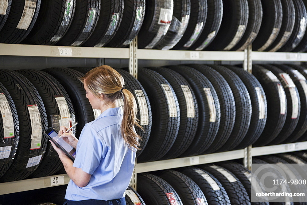 Young female mechanic takes inventory of new tires in repair shop