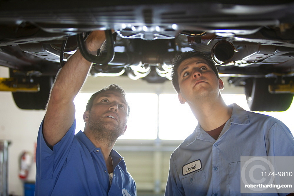 Two mechanics work on the underside of a care on a lift in a repair shop
