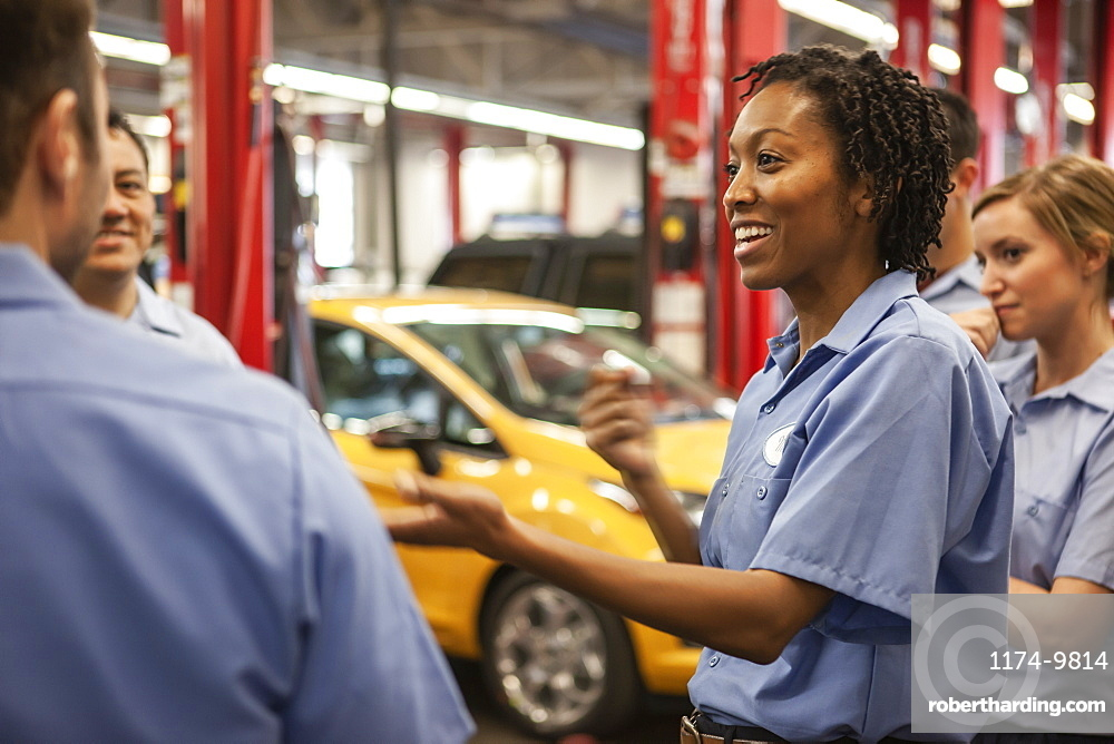 Team of mechanics working on a car discuss a problem in an auto repair shop
