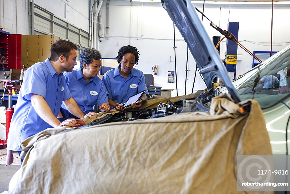 Three mechanics sharing a digital tablet and planning work on a car in for repair