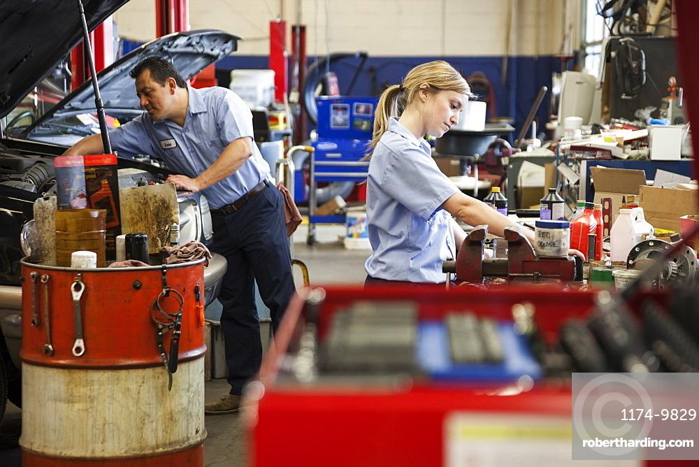 Caucasian female mechanic works on engine in auto repair shop