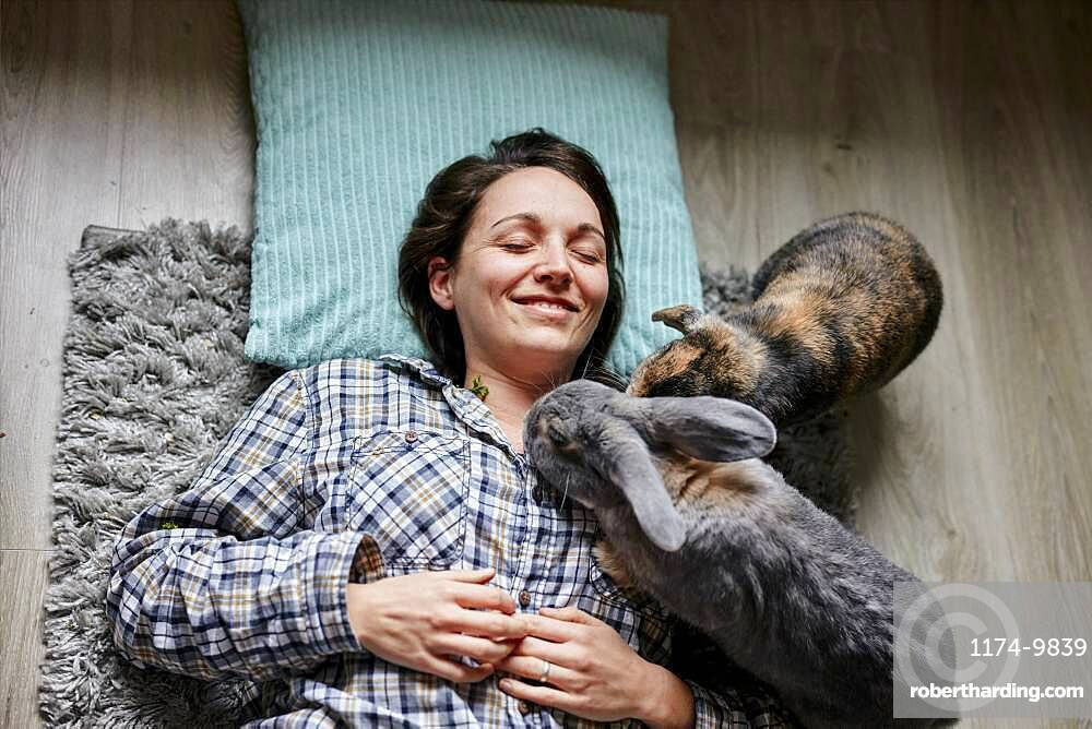 Woman lying on floor surrounded by two pet house rabbits shot from above, Bristol, United Kingdom