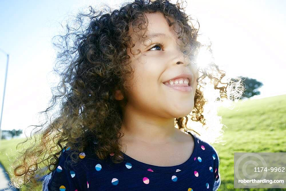 Young mixed race girl aged 4 outdoors,