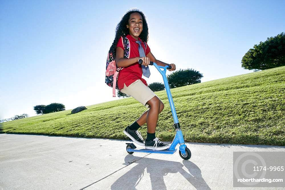 Young mixed race girl in pink shirt and formal tie, wearing a backpack on a scooter