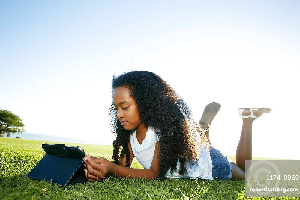 Nine year old mixed race girl lying on grass looking at a digital tablet.