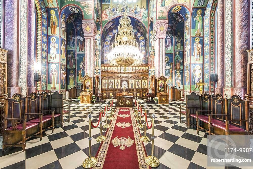 Serbian Orthodox church interior in Ljublijana, murals, painted pillars and walls, and chandelier.