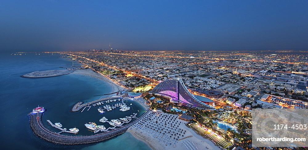 Cityscape of Dubai, United Arab Emirates at dusk, with coastline of Persian Gulf and marina in the foreground, Dubai, United Arab Emirates