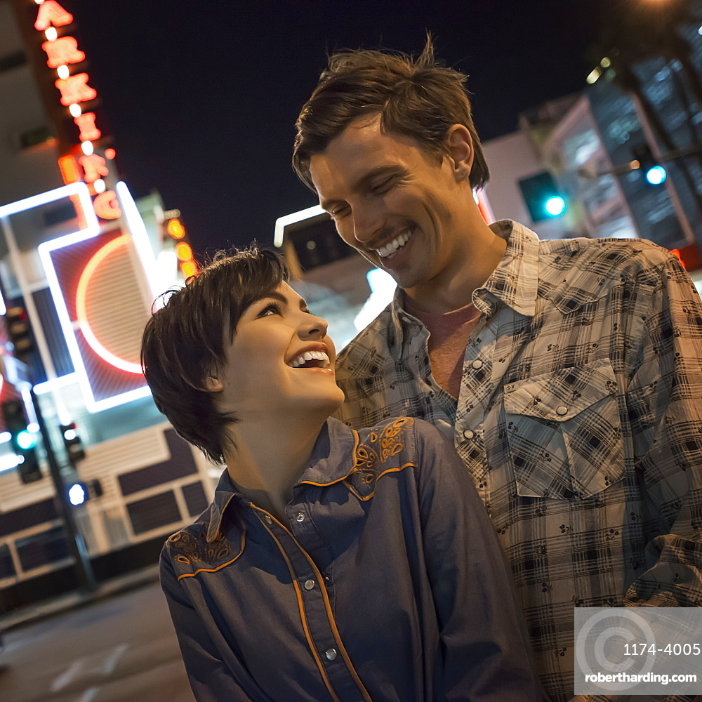 A couple, man and woman side by side in a city street at night. Neon signs, United States of America