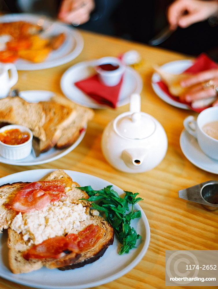 A table covered with plates of food. A cooked breakfast of bacon, eggs and toast and pot of tea. Two people seated , England