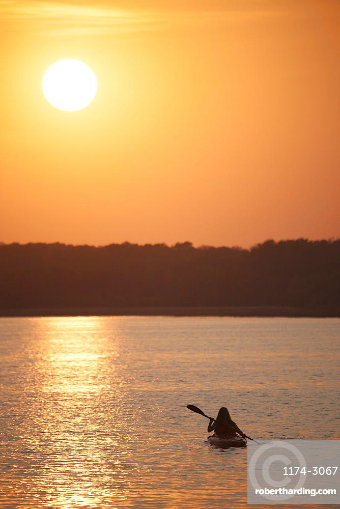 Kayaker at sunset on a calm lake, Kayaking at sunset, Saskatchewan, Canada