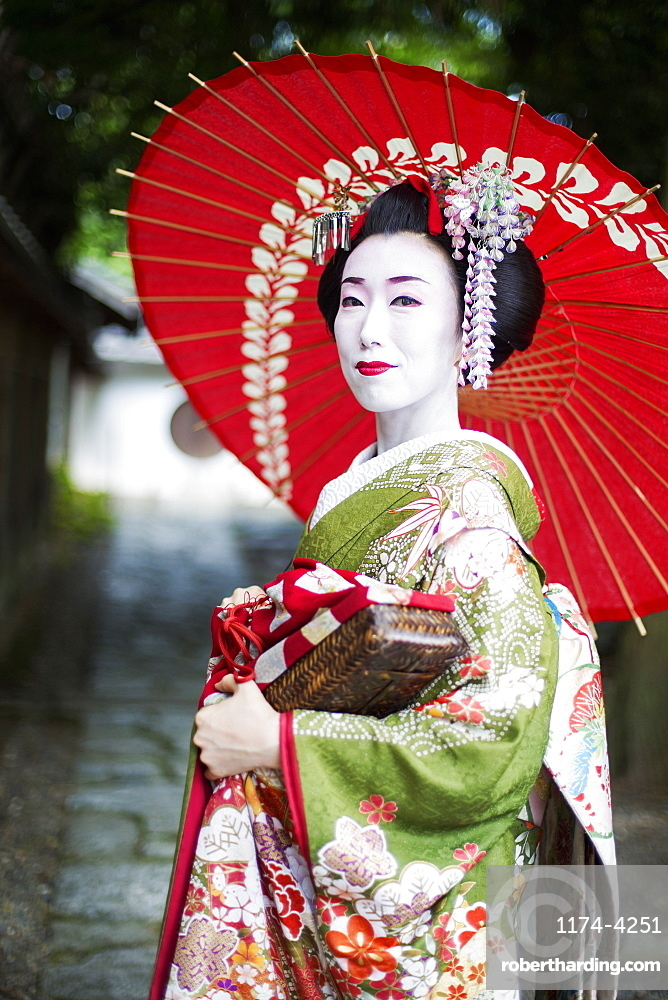 A woman dressed in the traditional geisha style, wearing a kimono and obi, with an elaborate hairstyle and floral hair clips, with white face makeup with bright red lips and dark eyes holding a red paper parasol, Japan