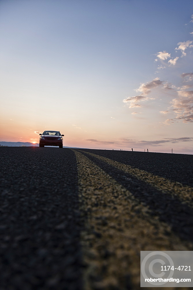 Low angle view looking up at a convertible sports car on the road at sunset, United States of America