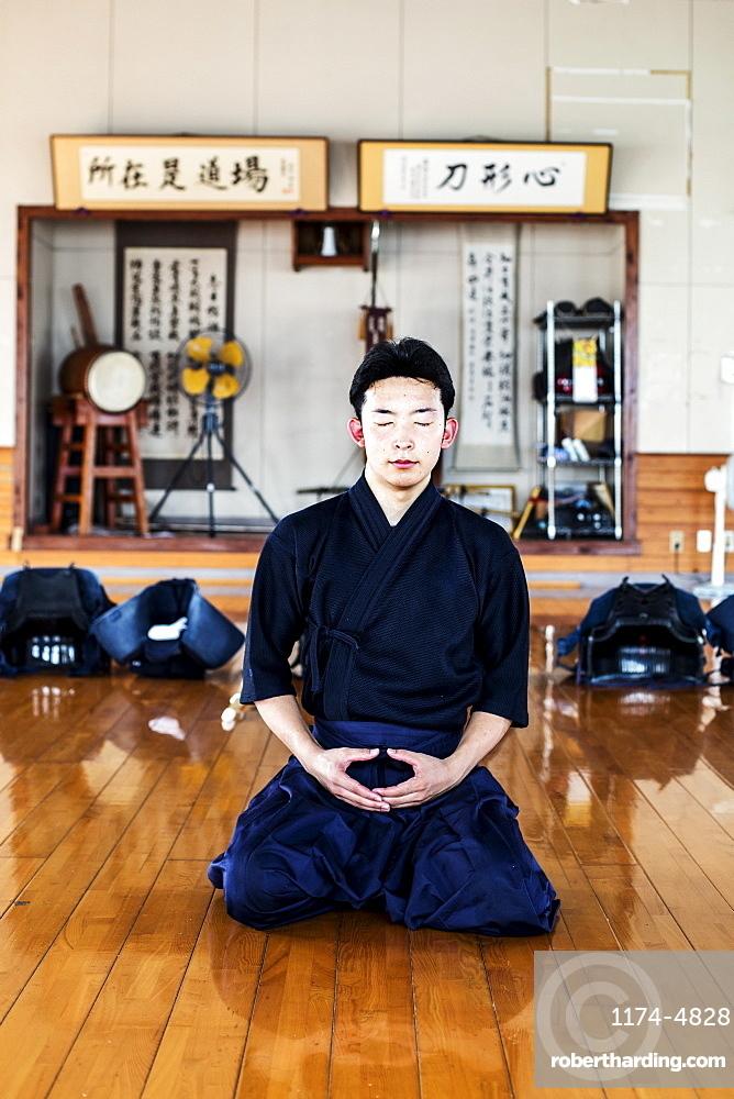 Male Japanese Kendo fighter kneeling on wooden floor, meditating, Kyushu, Japan