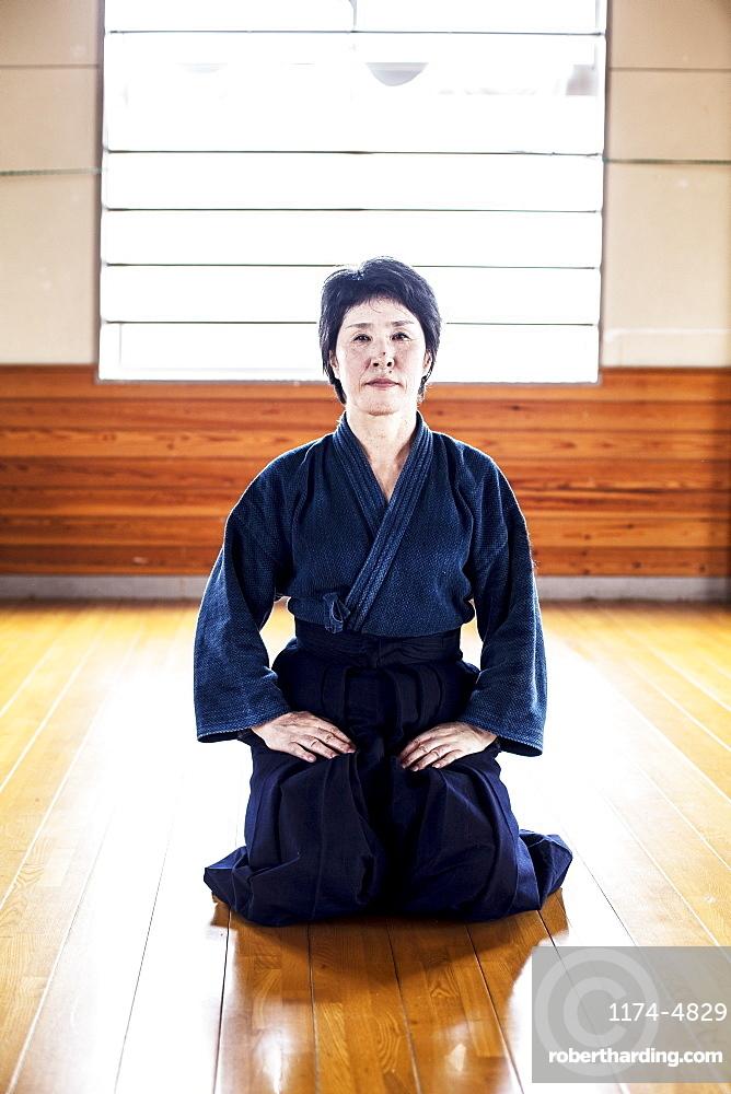 Female Japanese Kendo fighter kneeling on wooden floor, looking at camera, Kyushu, Japan