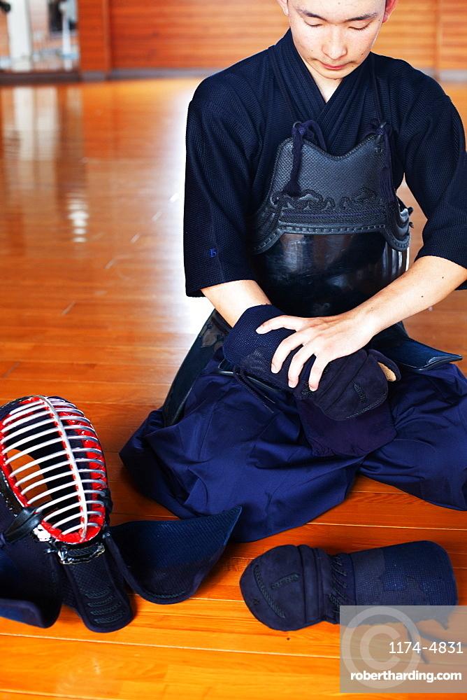 Male Japanese Kendo fighter kneeling on wooden floor, putting on Kote, hand protectors, Kyushu, Japan