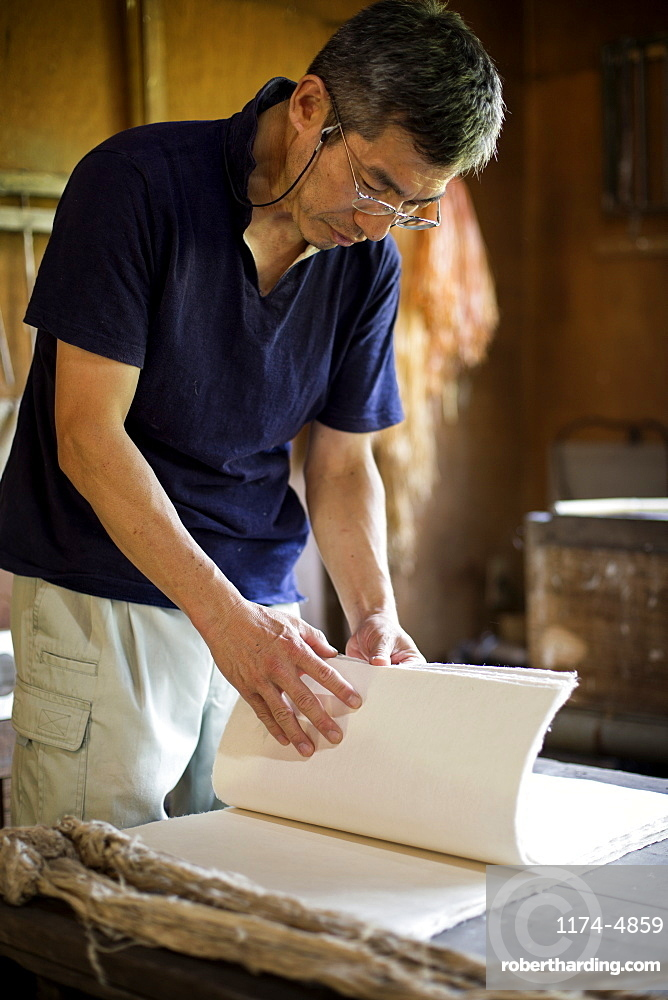Japanese man standing in a workshop,  checking through sheets of traditional Washi paper, Kyushu, Japan