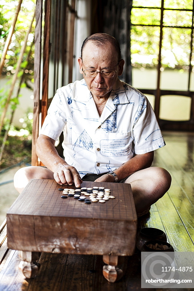 Japanese man sitting on floor on porch of traditional Japanese house, playing Go, Kyushu, Japan