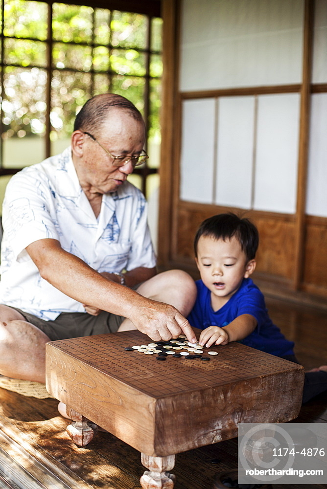 Japanese man and little boy sitting on floor on porch of traditional Japanese house, playing Go, Kyushu, Japan