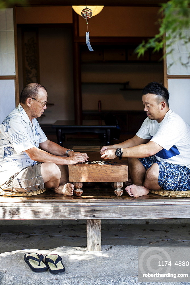 Two Japanese men sitting on floor on porch of traditional Japanese house, playing Go, Kyushu, Japan
