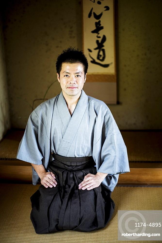 Japanese man wearing kimono sitting on floor in traditional Japanese house, looking at camera, Kyushu, Japan